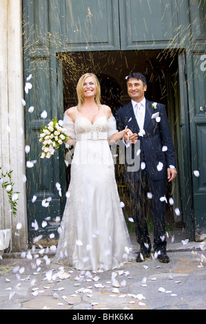 Newlyweds during rice and petal throwing after wedding ceremony - Stock Photo