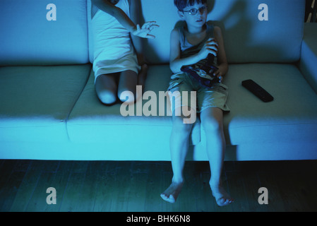 Boy playing video game, sister reaching for joystick - Stock Photo