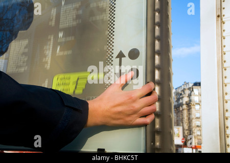 Person looking at and using push button to operate an interactive tourist / moving / information / street map of - Stock Photo