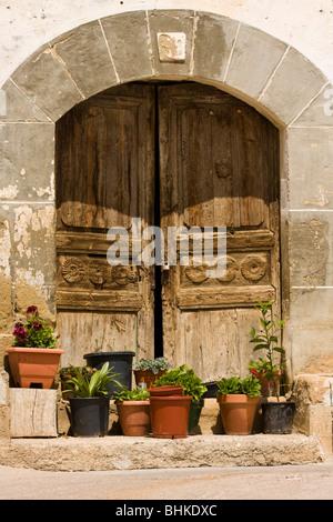 Old wooden door and entrance to building with pot plants, Las Penas de Riglos, Huesca Province, Aragon, Spain - Stock Photo