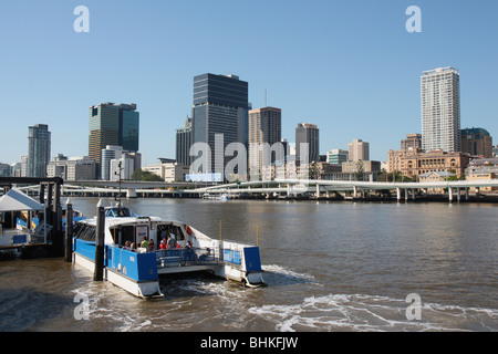 Brisbane City Centre and City Cat Ferry on Brisbane River in Queensland, Australia on a sunny day - Stock Photo