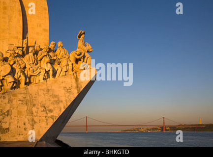 Portugal Lisbon Monument to the discoveries and suspension bridge in late evening light. - Stock Photo