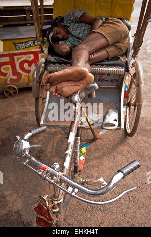 Indian cycle rickshaw wala taking time out in Puri, india. - Stock Photo