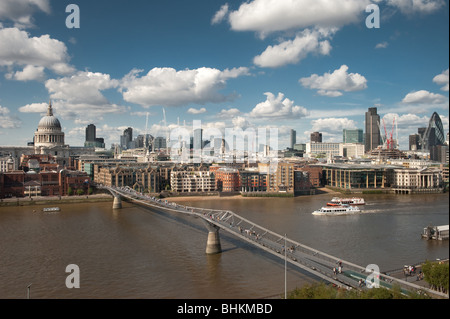 photograph of millenium bridge over river thames with city of london skyline - Stock Photo