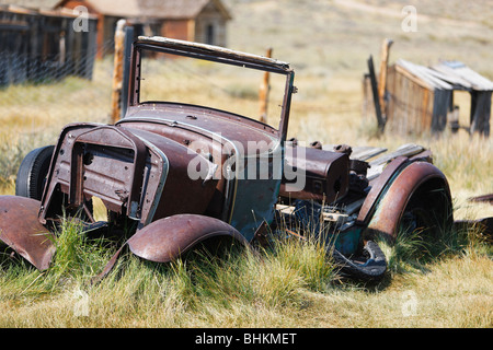 Old Car Frame is Rusting Away in Bodie Ghost Town, California - Stock Photo