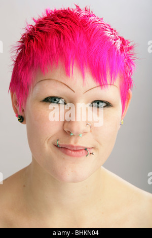 Pretty young woman with bright dyed hair looking at camera. - Stock Photo