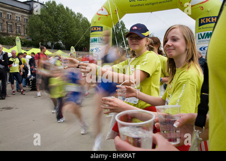 Two girls helping with water glasses for runners. Marathon in Dresden, Germany - Stock Photo