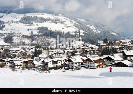 Skiers on the slopes above the centre of Kirchberg, near Kitzbuhel, Tyrol, Austria - Stock Photo