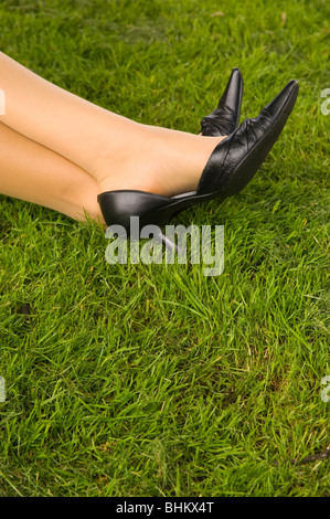 Business woman resting feet on the green grass - Stock Photo