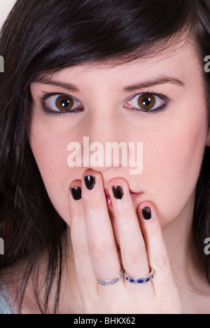 Beautiful young woman hand covering mouth - Stock Photo