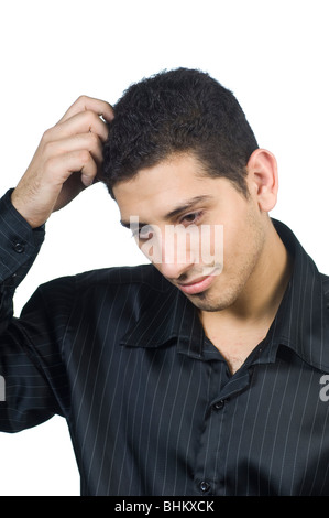Young man trying to remember while hand scratching his head against a white background - Stock Photo