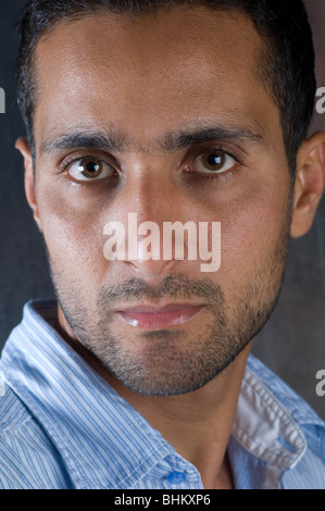 Closeup portrait of a young Arabic man looking at the camera - Stock Photo