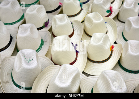 white straw sombreros with pretty feathers in their colored bands spread out for sale at Ocotlan Market Oaxaca Mexico - Stock Photo