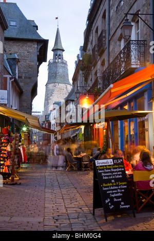 Dinan, Brittany, France. View along Rue de la Poissonnerie to the Tour de l'Horloge, dusk. - Stock Photo