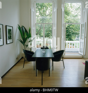 Black chairs and table in front of French windows in modern dining room with  wooden flooring - Stock Photo