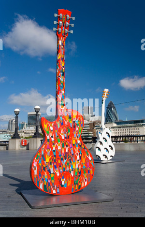 London, Greater London, England. Colourful replica guitars on display on the South Bank near Tower Bridge. - Stock Photo