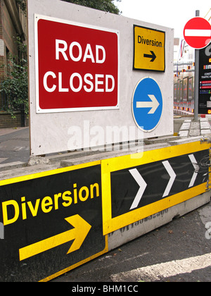 Road signs including road closed, diversion, arrows, no entry and chevrons blocking a trough road - Stock Photo