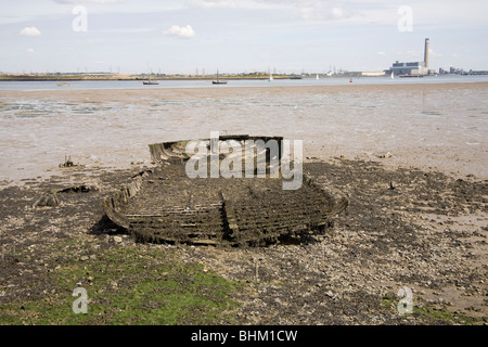 Remains of a barge on the bank of the Medway with Kingsnorth Power Station in the background - Stock Photo