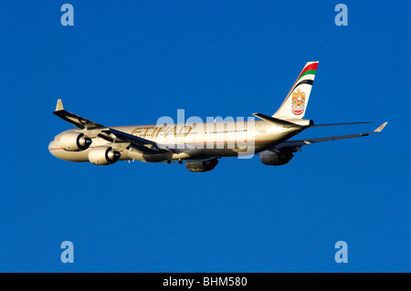 Airbus A340 operated by Etihad Airways climbing out from take off at London Heathrow Airport. - Stock Photo