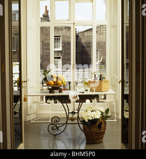 View through double doors of bowl of fruit on marble-topped metal table in front of French windows in townhouse - Stock Photo