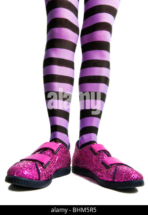 Pink sparkle shoes with woman legs in purple striped tights or pantyhose - Stock Photo