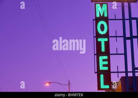 Turquoise neon Motel sign at the Orchard Inn along Historic US Route 66 at dusk with purple sky. Kingman Arizona - Stock Photo