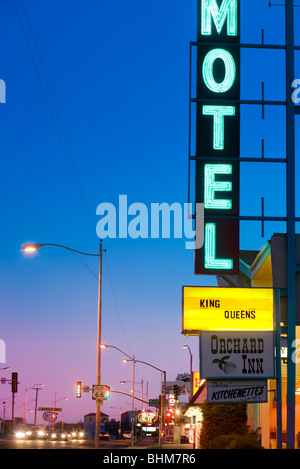 Neon Motel sign at the Orchard Inn in Kingman Arizona along historic US Route 66. Route 66 shield in front. At dusk. - Stock Photo