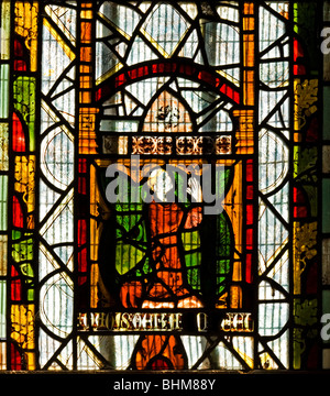 Medieval stained glass depicting a male kneeling in prayer - Stock Photo