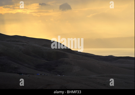Sunset at Dead Sea with a Bedouin camp seen from Jordan - Stock Photo