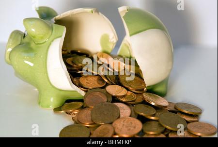 Broken piggy bank with coins - Stock Photo