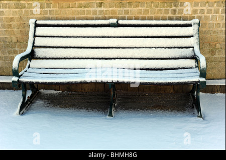 Snow covers a bench on brighton seafront - Stock Photo