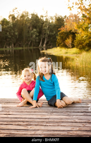 little sisters sitting on lake dock - Stock Photo