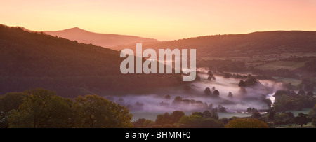 Mist lingers in the Usk Valley at dawn looking towards Sugar Loaf mountain, Brecon Beacons National Park, Powys, - Stock Photo