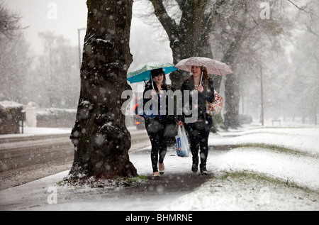 Two girls walking through a snow storm in Malvern, UK - Stock Photo