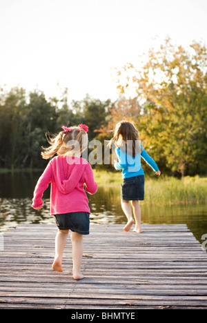 2 sisters running on  lake dock - Stock Photo