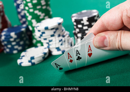 Gambler checking at his four aces - Stock Photo