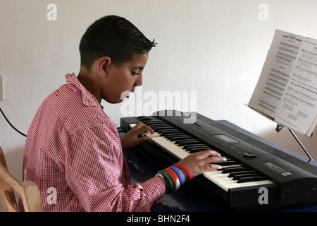 Teenage boy making music  at synthesizer keyboard - Stock Photo