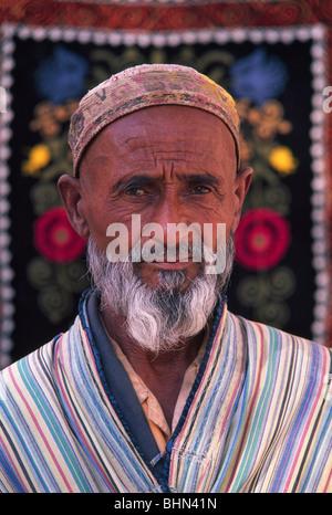 Uzbek man in traditional costume with colorful carpet, Samarkand, Uzbekistan - Stock Photo