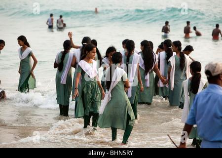 India, Kerala, Kovalam, Hawah (Eve) Beach, Indian schoolgirls in shalwar kameez uniform bathing in sea - Stock Photo