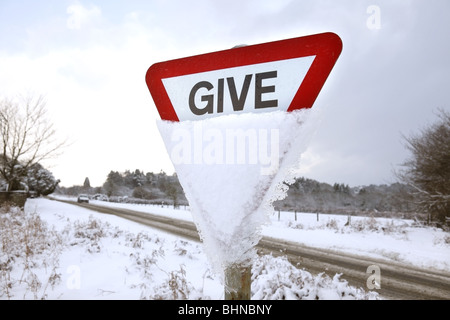 Give way sign in the snow. - Stock Photo