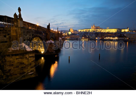 View of Karlův most (Charles Bridge) and Pražský hrad (Prague Castle) from the bank of the River Vltava at dusk. - Stock Photo