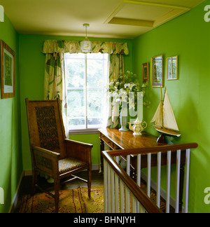 antique chair and table in front of window with floral curtains on bright green landing