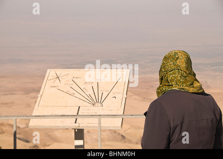 Woman looking to a Sign board pointing to the promised land at mount Nebo, Jordan, Asia. - Stock Photo