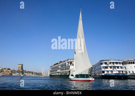 New vs old - Felucca vs cruiseship in Aswan, Egypt - Stock Photo