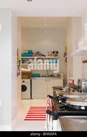 Running-bond tiled kitchen with aga and striped rug - Stock Photo