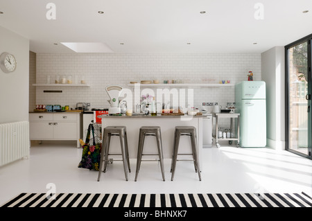 Open plan white-tiled kitchen with barstools and retro fridge - Stock Photo