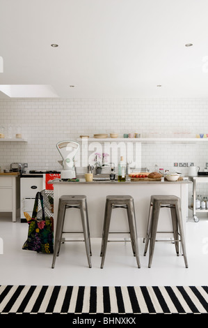 White tiled kitchen with barstools, striped runner rug and retro weighing scales - Stock Photo