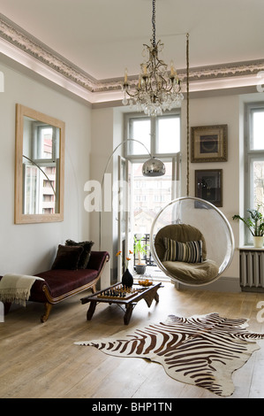 eero aarnio bubble chair in living room with zebra skin rug and chandelier stock photo