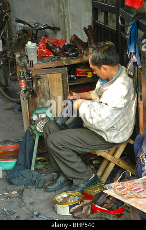 Chinese shoemaker fixing shoes in his street workshop at Shanghai, China - Stock Photo