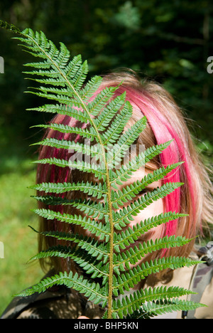 a young girl with pink dyed hair in bob hides behind a bright green fern leaf that partly obscures her face - Stock Photo